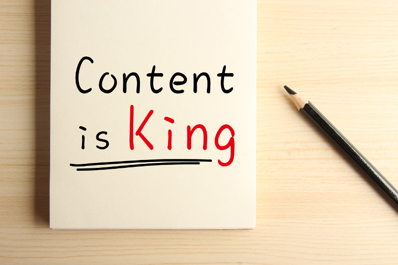 Text Content is King with underline on the notebook with a pencil aside.